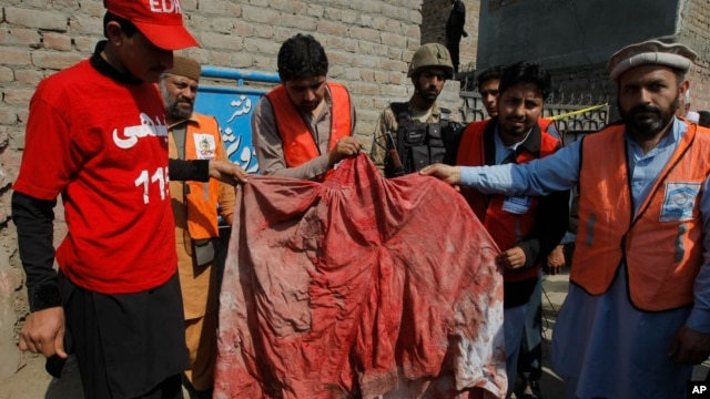 Pakistani volunteers show a blood-soaked burqa of a woman who was killed in an a suicide bombing in the town of Shabqadar, Charsadda district, Pakistan, March 7, 2016.