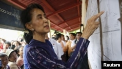 Myanmar pro-democracy leader Aung San Suu Kyi checks a voters list during her door-to-door visits for voter education campaign at Warheinkha village, in her constituency town Khawhmu, outside Yangon on July 4, 2015. Suu Kyi's National League for Democracy