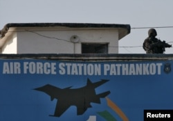 FILE - An Indian security personnel stands guard on a building at the Indian Air Force (IAF) base at Pathankot in Punjab, India, Jan. 5, 2016.