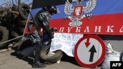 Một người đàn ông vũ trang thân Nga đặt 1 biểu ngữ tại 1 trạm kiểm soát bên ngoài thành phố Slavyansk, miền đông Ukraine, 26/4/2014