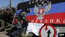 Pria bersenjata pro-Rusia di sebuah pos pemeriksaan di luar kota Slavyansk, Ukraina timur (26/4). (AFP/Max Vetrov)