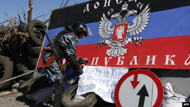 A pro-Russian armed man displays a banner at a check point outside the eastern Ukrainian city of Slavyansk, Apr. 26, 2014.