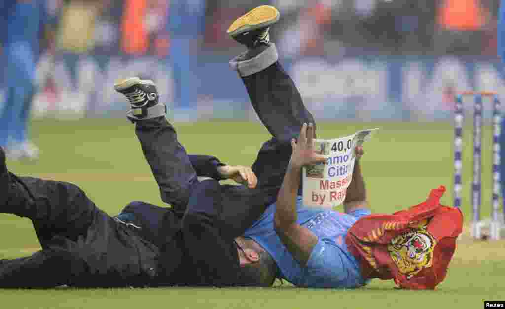 A protester is tackled to the ground after running onto the field holding a sign protesting against Sri Lanka's President Mahinda Rajapaksa during the ICC Champions Trophy semi-final match between Sri Lanka and India at Cardiff Wales Stadium in Wales, Britain.