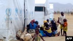 Para pengungsi Nigeria duduk di samping tenda UNHCR di kamp pengungsi di Minawao, di perbatasan Nigeria (29/3/2014).
