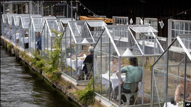 Klientët drekojnë të mbyllur në kuti xhami në restorantin Mediamatic në Amsterdam, Hollandë