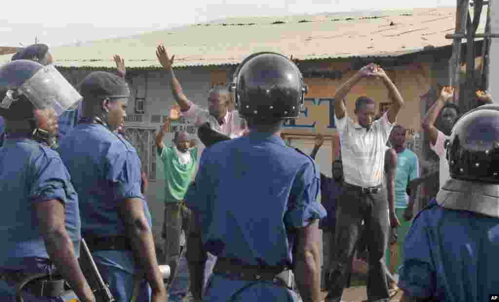 Mains levées, des manifestants font face à la police anti-émeute qui tentent de les disperser à Bujunmbura, Burundi, lundi 27 avril 2015.