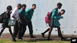 FILE - Students leave school at the end of the day in a suburb of Johannesburg, South Africa.