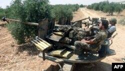 Des combattants rebelles utilisant une batterie anti-aérienne, près de Hama, en Syrie.