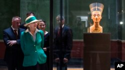 FILE - Queen Margrethe II of Denmark looks at the bust of Nefertiti, as she visits the New Museum in Berlin, Sept. 10, 2014.