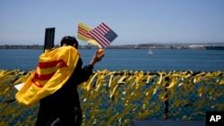 Ảnh minh hoạ: Một người Việt tị nạn cầu nguyện cho đất nước cạnh hàng rào với 60,000 nơ vàng vinh danh những người hy sinh trong chiến tranh Việt Nam trên hàng không mẫu hạm USS Midway ở San Diego, ngày 26/4/2015.