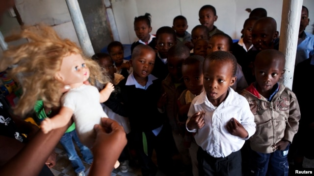 FILE - A volunteer from Simelela, an organization dealing with sexual violence, uses a doll to teach children about inappropriate touching and sexual abuse, at a pre-school in Cape Town's Khayelitsha township.