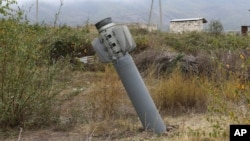 An unexploded projectile of multiple rocket launcher stuck into land near a settlement in self-proclaimed Republic of Nagorno-Karabakh, Azerbaijan, Oct. 1, 2020.