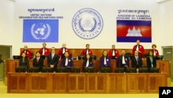 In this photo released by the Extraordinary Chambers in the Courts of Cambodia, Judges and clerks of the U.N.-backed war crimes tribunal are standing inside the court hall of the U.N.-backed war crimes tribunal in Phnom Penh, Cambodia, Thursday, Aug. 7, 2