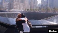 دو نفر از بازماندگان حملات تروریستی ۱۱ سپتامبر مقابل بنای یادبود ساخته شده به جای دو برج دو قلوی مرکز تجارت جهانی نیویورک