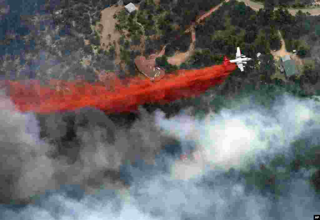 An aircraft lays down a line of fire retardant between a wildfire and homes in the dry, densely wooded Black Forest area northeast of Colorado Springs, Colorado, June 13, 2013.
