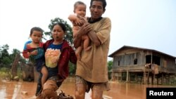 Parents carry their children as they leave their home during the flood after the Xepian-Xe Nam Noy hydropower dam collapsed in Attapeu province, Laos
