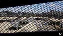A view through a mesh window looks out over part of Aden Central Prison, known as Mansoura, in this May 9, 2017, photo in Aden, Yemen. A section of the prison is run by Yemeni allies of the United Arab Emirates, part of a network of secret prisons in southern Yemen where hundreds of people detained in the hunt for al-Qaida militants over the past year have disappeared.