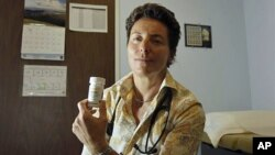 Dr. Lisa Sterman holds a bottle of Truvada pills that she prescribes for about a dozen patients at high risk for developing AIDS, at her office in San Francisco, May 10, 2012.