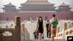 Para pengunjung mengenakan masker untuk melindungi dari penularan virus corona di Kota Terlarang, Beijing, 1 Mei 2020. (Foto: AP)