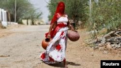 一名印度女子拿着罐子去打水