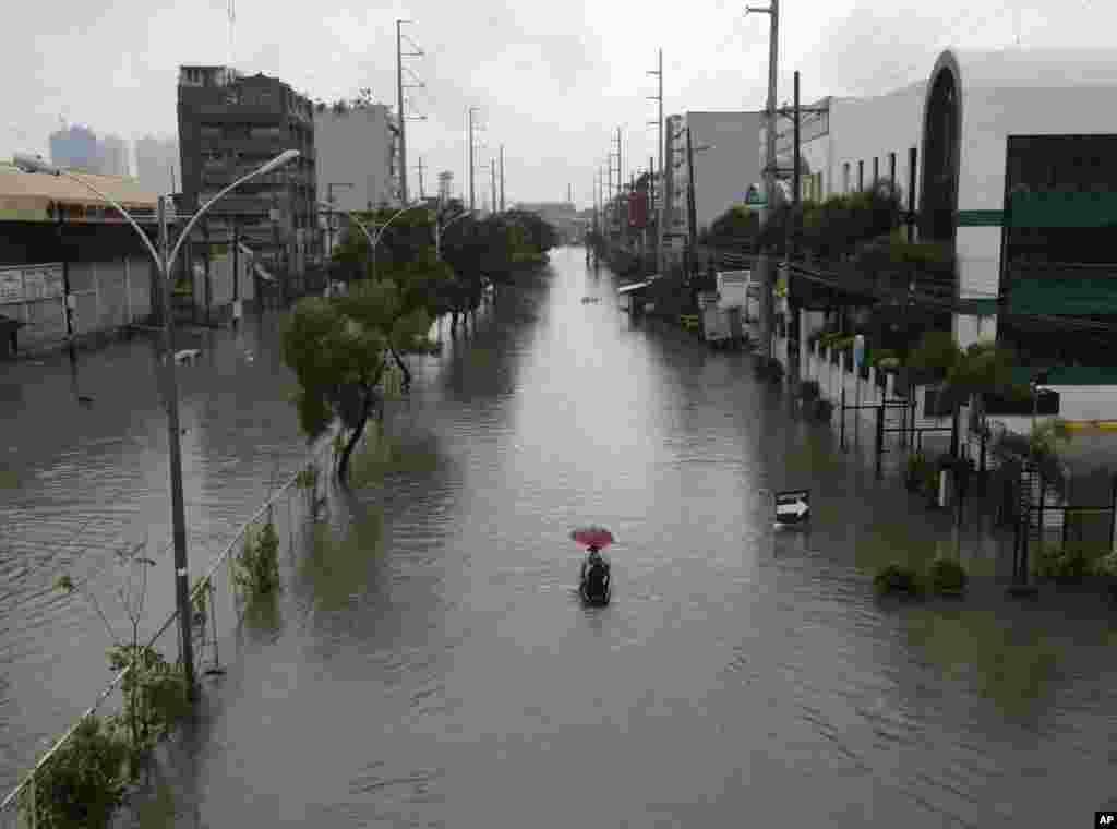 Warga menggunakan perahu kecil untuk transportasi di jalan yang terkena banjir akibat Topan Usagi di pinggir kota Quezon city, timur laut Manila (23/9). (AP/Bullit Marquez)