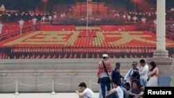 "Para pengunjung beristirahat di depan layar lebar yang menayangkan video propaganda di Lapangan Tiananmen di Beijing (31/5). Kelompok aktivis ""Para Ibu Tiananmen"" menuntut agar para pemimpin China memulai dialog dan menilai kembali penindakan di Lapangan Tiananmen di Beijing tanggal 4 Juni 1989, yang menewaskan hampir tiga ribu pemrotes."