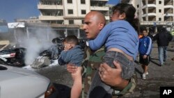 A Lebanese army soldier carries two injured children away from the site of an explosion near the Kuwaiti Embassy and Iran's cultural center, in the suburb of Beir Hassan, Beirut, Lebanon, Wednesday, Feb. 19, 2014. The bombing in a Shiite district in south
