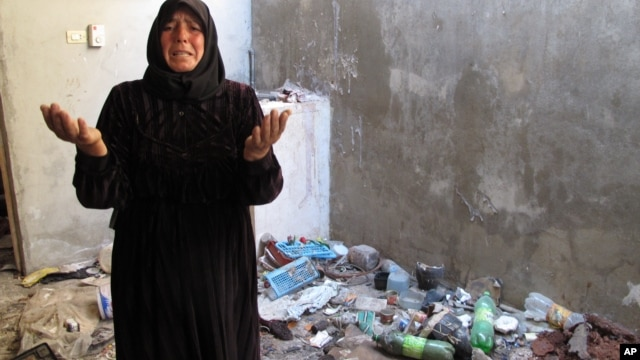 A resident of Bustan al-Qusr complains about trash left in her home by Syrian soldiers who took over her house during summer fighting in Aleppo, August 5, 2012.