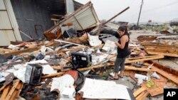 Jennifer Bryant melihat puing-puing kantor milik keluarganya yang rusak dihantam badai Harvey, 26 Agustus 2017 di Katy, Texas. (AP Photo/David J. Phillip)
