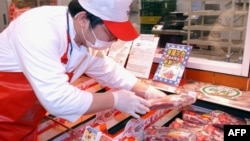 A staff member at a Taipei hyper market examines imported U.S. beef. (File Photo)