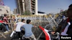 حامیان مقتدی صدر، روحانی پرنفوذ شیعه عراقی سعی دارند سیم های خاردار در منطقه سبز بغداد را بردارند - ۲۸ اسفند ۱۳۹۴