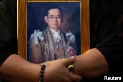 A mourner holds a portrait of Thailand's late King Bhumibol Adulyadej in Bangkok, Thailand, Oct. 14, 2016.
