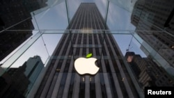 FILE - The leaf on the Apple symbol is tinted green at the Apple flagship store on 5th Ave in New York, April 22, 2014.
