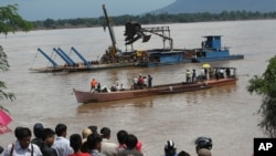 FILE - Onlookers watch the search operation for the lost Lao Airlines plane on the banks of the Mekong River in Pakse, Laos, Oct. 17, 2013.