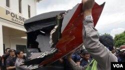 Polisi Indonesia mengangkat puing-puing pesawat yang ditemukan di sekitar Pulau Batam, Indonesia, Kamis 4 November 2010.
