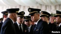 Para pilot Malaysia Airlines dalam upacara penghormatan bagi mendiang ko-pilot Eugene Choo, saat jenazahnya kembali ke Seremban (2/9). (Reuters/Olivia Harris)