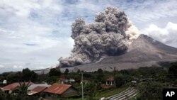 Gunung Sinabung memuntahkan abu vulkanik terlihat dari desa Tiga Serangkai, Sumatra Utara, 1 April lalu (foto: dok).