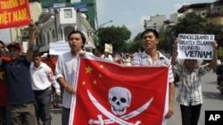 2011年6月19日越南抗议者手举画有海盗图样的中国国旗在河内举行示威(资料照片)