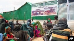 Somalis queue outside a temporary feeding center run by an Islamic charitable group at a Mogadishu IDP camp