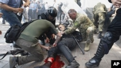 Cảnh sát giúp một người biểu tình bị thương trong vụ nổ ở Kyiv, ngày 31/8/2015.