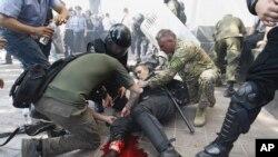 Seorang polisi Ukraina terluka akibat ledakan granat ketika terjadi bentrokan dengan para demonstran di Kyiv, Senin (31/8).