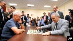 World Chess Champion Garry Kasparov, right, and Rex Sinquefield, founder and president of the Board of Directors of the St. Louis Chess Club, kick-off the first-ever Congressional Chess Match at the Rayburn House Office Building in Washington, D.C., June 18, 2014.