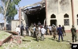 Soldiers stand guard outside St. Rita's Catholic church following a suicide bombing in Kaduna, Nigeria, Oct. 28, 2012.