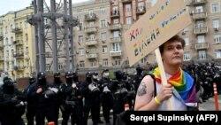 Seorang aktivis LGBTQ tampak berdiri di dekat rombongan polisi yang mengawal aksi pawai Pride di ibu kota Ukraina, Kiev, pada 19 September 2021 (Foto: AFP/Sergei Supinsky)