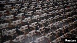 មនុស្សម្នាពាក់ម៉ាស់ធ្វើការនៅមជ្ឈមណ្ឌលដេញថ្លៃផ្កា បន្ទាប់ពីមានការផ្ទុះឡើងនូវមេរោគកូរ៉ូណាវីរុស នៅក្នុងប្រទេសចិន ក្នុងក្រុង Kunming ខេត្ត Yunnan ប្រទេសចិន កាលពីថ្ងៃទី១០ ខែកុម្ភៈ ឆ្នាំ២០២០។