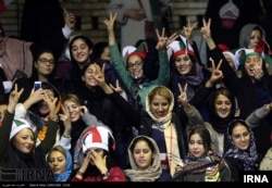 Iranian women watch the Iranian men's basketball team play Iraq in a FIBA World Cup Asian Qualifier at Azadi Indoor Stadium in Tehran, Feb. 25, 2018.
