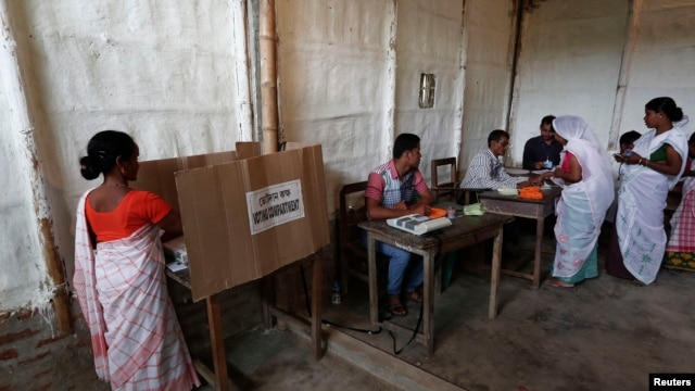 A woman (L) casts her vote with an electronic voting machine as others get their voting slip from an officer at a polling station in Majuli, a large river island in the Brahmaputra river, Jorhat district, in the northeastern Indian state of Assam, April 7