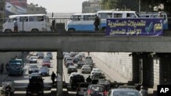 "Egyptians drive past a banner calling for a ""yes"" vote in a referendum on constitutional changes scheduled for Saturday, Cairo, March 17, 2011"
