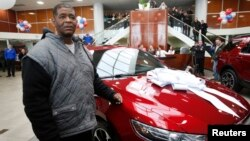 Detroit resident James Robertson reacts next to the 2015 red Ford Taurus sedan he was surprised with as a free gift at the Suburban Ford dealership in Sterling Heights, Michigan, Feb. 5, 2015.