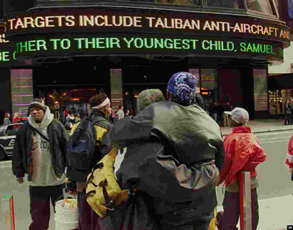 People watch the news on an electronic billboard at Times Square in New York on October 7, 2001, the day that American and British forces unleashed missile attacks against military targets and Osama bin Laden's training camps inside Afghanistan. (AP)